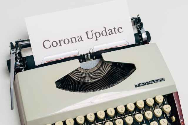 a vintage typewriter with corona update typed on white paper